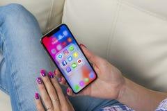 苹果计算机iPhone x在有社会媒介facebook, instagram,慌张,在屏幕上的snapchat应用象的妇女手上  社会medi 免版税库存图片