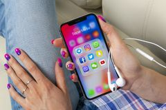 苹果计算机iPhone x在有社会媒介facebook, instagram,慌张,在屏幕上的snapchat应用象的妇女手上  社会medi 免版税库存照片