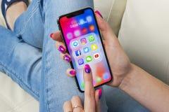 苹果计算机iPhone x在有社会媒介facebook, instagram,慌张,在屏幕上的snapchat应用象的妇女手上  社会medi 库存照片