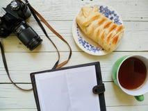苹果饼、一杯茶,笔记本和一台老影片照相机 免版税库存图片