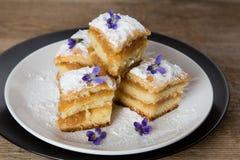 苹果饼片断与紫罗兰的在上面 免版税库存图片