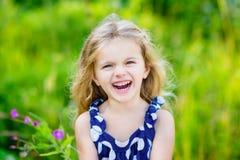 范妮和美丽的笑的小女孩有长的金发的 免版税库存照片