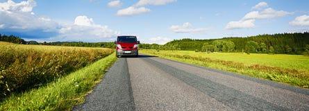 范, suv,驾驶一条长的乡下公路 库存图片