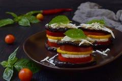 从茄子、夏南瓜、蕃茄和年轻乳酪的开胃菜在黑暗的背景 素食食物 ratatouille 库存照片
