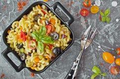茄子、橄榄和蕃茄挤过去通心面面团,在一个黑服务盛肉盘 库存照片