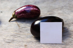 茄子和卡片在木书桌上 图库摄影