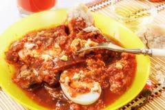茄子和被炖的菜蔬菜炖肉用煮沸的鸡蛋 与鸡蛋片断的一把叉子  新鲜的汁液和面包 免版税库存图片