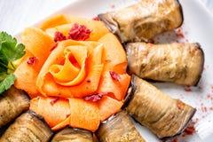 茄子滚动用乳酪,并且红萝卜象在有选择聚焦和顶视图的白色板材上升了 免版税图库摄影
