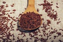 茉莉花在一把木匙子的糙米在自然餐巾特写镜头 图库摄影