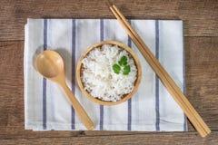 茉莉花白米,煮熟的白米,烹调了在木碗的简单的米有匙子和筷子的,在土气的有机米 免版税库存照片
