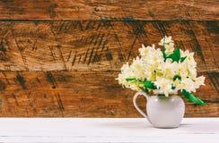 茉莉花花束在一张白色桌上的一个水罐开花在棕色木减速火箭的背景 图库摄影