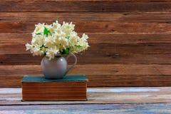茉莉花花束在一本旧书的一个水罐开花在棕色木减速火箭的背景的一张桌上 免版税库存图片