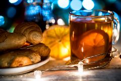 茶、圣诞灯和酥皮点心舒适静物画  免版税库存照片