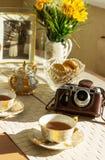 茶、夏天黄色花、老foto和葡萄酒照相机在木背景 免版税库存图片