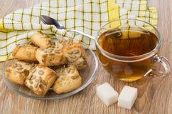 茶、多块的糖、板材用曲奇饼,餐巾和茶匙 库存照片