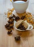 茶、干桂香、素食主义者曲奇饼和茴香在木backgro 库存图片