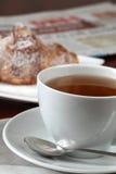 茶、新月形面包和报纸 库存图片