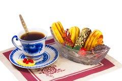 茶、糖果和蛋糕在一个柳条筐。 免版税库存图片