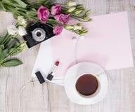 茶、花、葡萄酒照相机、耳机,唇膏和她 免版税库存图片