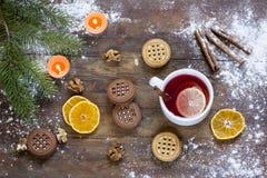 茶、蜜桔和曲奇饼在圣诞节装饰与圣诞树、坚果和苹果在黑暗的木背景说明对编辑:索引 免版税库存照片