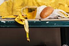 茶、面包和香蕉在杂乱内部剥皮 库存照片