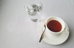 茶与水glas的在白色背景中 免版税图库摄影