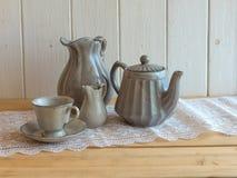 茶具是灰色的在木背景 茶壶,盛奶油小壶,杯和 库存照片