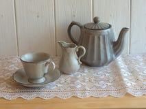 茶具是灰色的在木背景 茶壶,盛奶油小壶,杯和 免版税库存照片