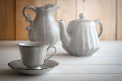 茶具是灰色的在木背景 茶壶,盛奶油小壶,杯和 免版税图库摄影