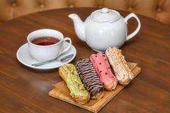 茶和五颜六色的小饼结块与奶油在木板 免版税库存图片