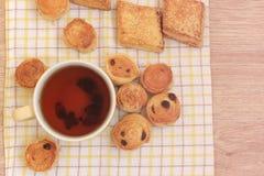 茶和小圆面包在木桌上 免版税图库摄影