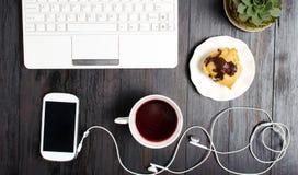 茶和点心在一张桌上与膝上型计算机 免版税库存图片