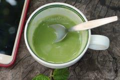 绿茶和牛奶在木背景 免版税库存图片