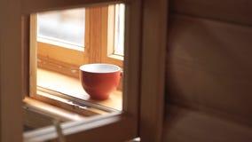 茶在一块木窗口基石的 茶在木窗台的 刹车与一个杯子的时间咖啡和城市视图 免版税图库摄影