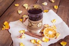 茶在沿海航船,干桔子,在木背景的干玫瑰花瓣的 库存照片
