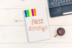 茶在笔记薄的在早晨和文本:Felize多明戈 愉快的星期天用西班牙语 库存照片