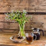 茶壶、杯子发球区域,板材用曲奇饼和有花的一个花瓶以老木墙壁为背景 免版税库存照片