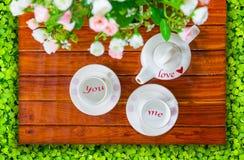茶壶、空的茶杯和人造花 库存图片
