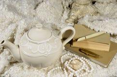 茶壶、羊毛织品和书 库存照片