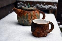 茶壶和一杯茶在第一雪的 免版税图库摄影