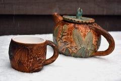 茶壶和一杯茶在第一雪的 免版税库存照片