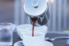 茶壶和咖啡特写镜头在一个白色杯子 免版税库存图片