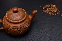 茶壶和干茶叶在黑板岩板或盘子 免版税库存照片