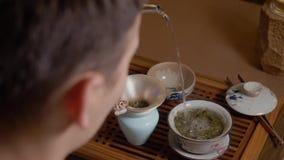 茶大师倾吐从水壶的面汤到gaiwan 从热的杯子的蒸汽 绿茶 影视素材
