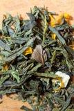 茶宏观照片  干木槿花堆的构成位于一个木板的  与叶子的绿色自然茶 库存图片
