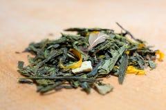 茶宏观照片  干木槿花堆的构成位于一个木板的  与叶子的绿色自然茶 免版税库存图片