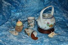 茶定期的茶壶、杯子、茶和蜡烛 免版税库存照片