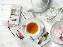 茶报纸简单手表的信息放松概念 免版税图库摄影