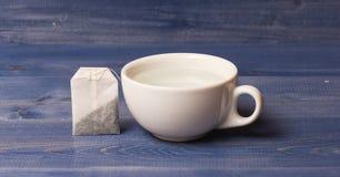 茶时间概念 杯或白色瓷杯子有透明热水和袋子的茶 酿造茶的过程  图库摄影