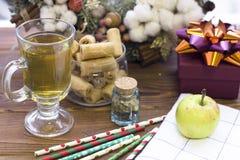 茶杯、一个绿色苹果、礼物盒、被仿造的秸杆和圣诞节花圈 库存图片